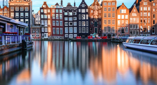 Narrows houses on Amsterdam canals with boats