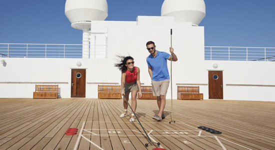 Couple play shuffleboard on QM2's deck small